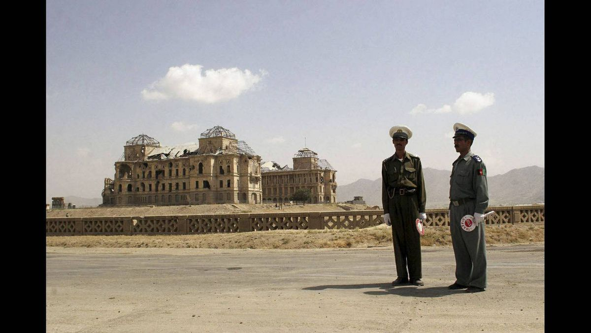 Afghan traffic police officers stand near the destroyed King's Palace in Kabul, August 29, 2005.