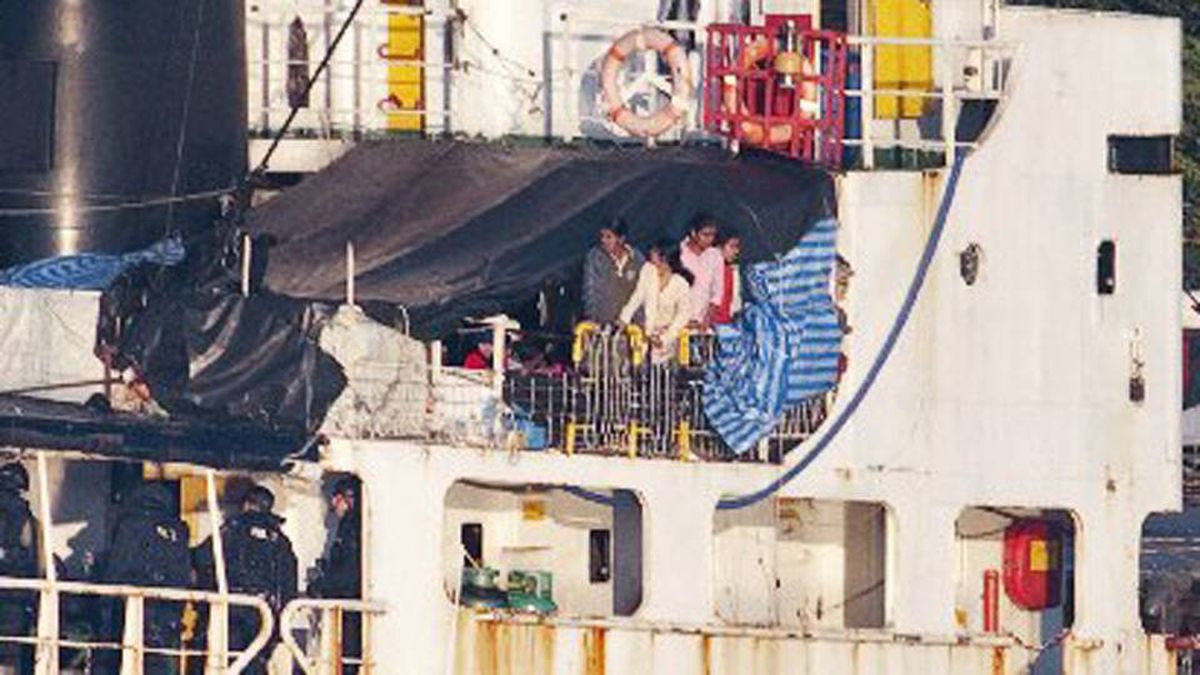 Some of the estimated 490 people thought to be Tamil migrants aboard the ship MV Sun Sea peer out from underneath a tarp after Canadian Border officials and police brought the ship into Canadian Forces Base Esquimalt in Colwood, B.C. on Vancouver Island on Friday.