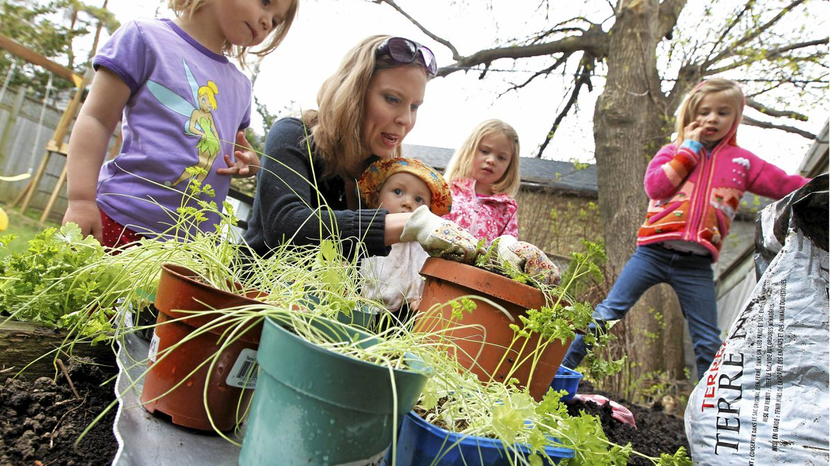 Patti Tinholt gardening in the back yard of her Toronto home with her four children on May 6, 2011. (Photo by Peter Power/The Globe and Mail)