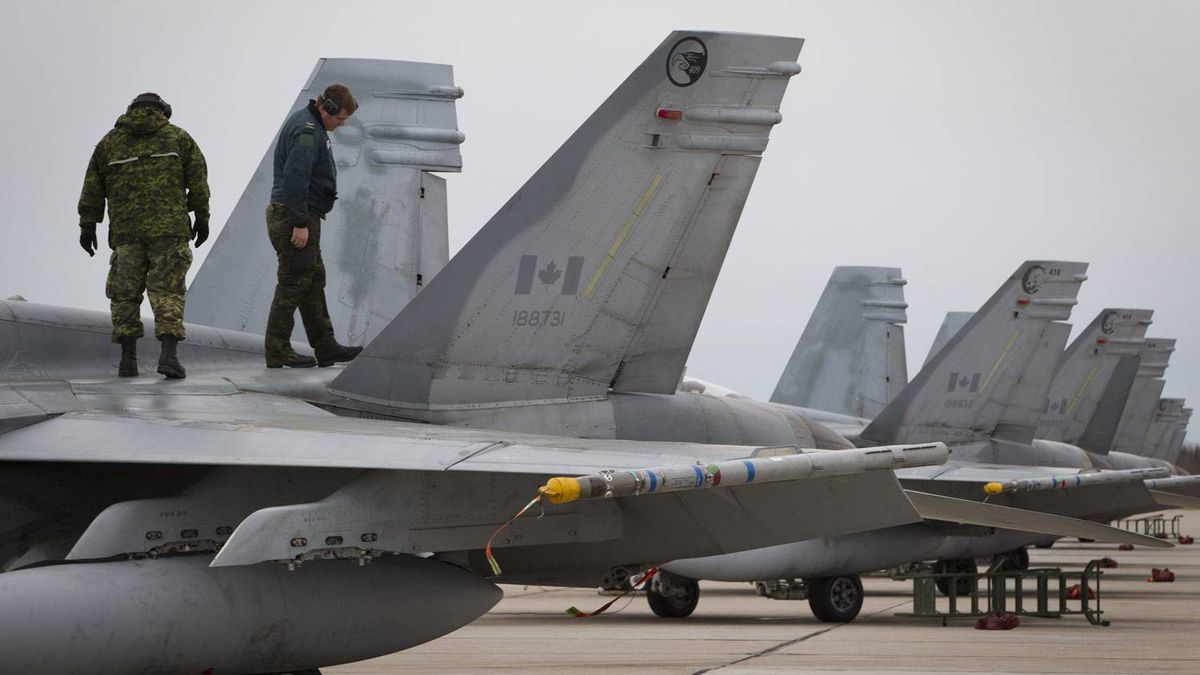 MCpl Robert Olivier, left, and Pte Gary Dunn look over a CF-18 at CFB Cold Lake during a routine inspection.
