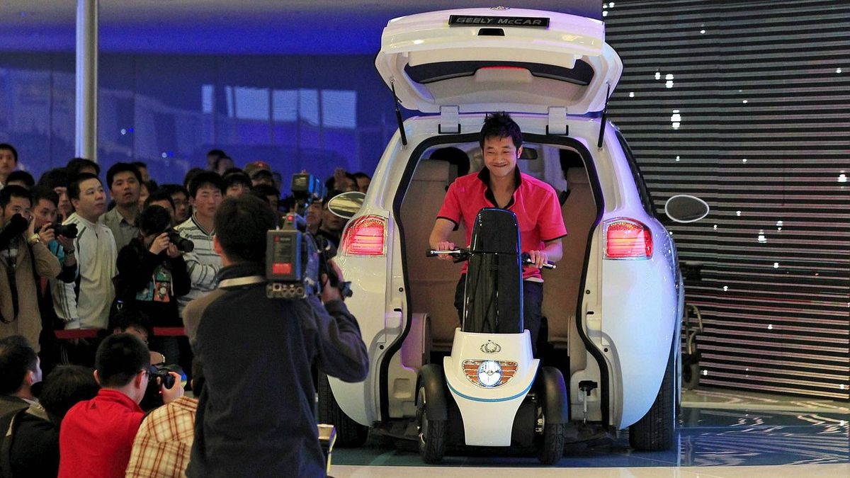 A model drives out from the back of the new Geely concept car McCar during a Geely presentation on the press day at the Shanghai International Auto Show Tuesday, April 19, 2011 in Shanghai, China. (AP Photo/Eugene Hoshiko)