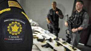 Police officers and Canadian Border Services agents display a seized cache of guns and illegal drugs in Brampton, Ont., on May 21, 2007.