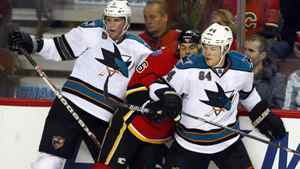 San Jose Sharks' Colin White, left, and Jamie McGinn sandwich Calgary Flames' Tom Kostopoulos.