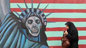 An Iranian woman walks past an anti-U.S. mural painted on the wall of the former American embassy in Tehran on Nov. 19, 2011.
