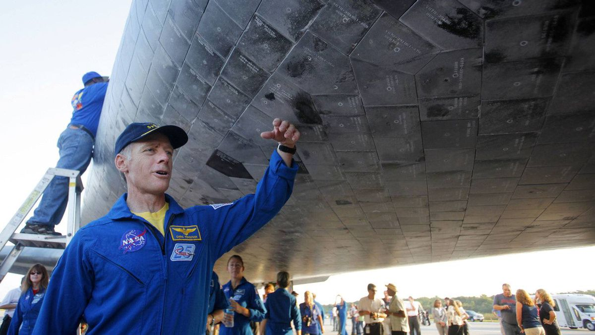 Space shuttle Atlantis commander Chris Ferguson touches tiles on the underside of the shuttle on July 21, 2011 at Kennedy Space Center in Florida after Atlantis landed.