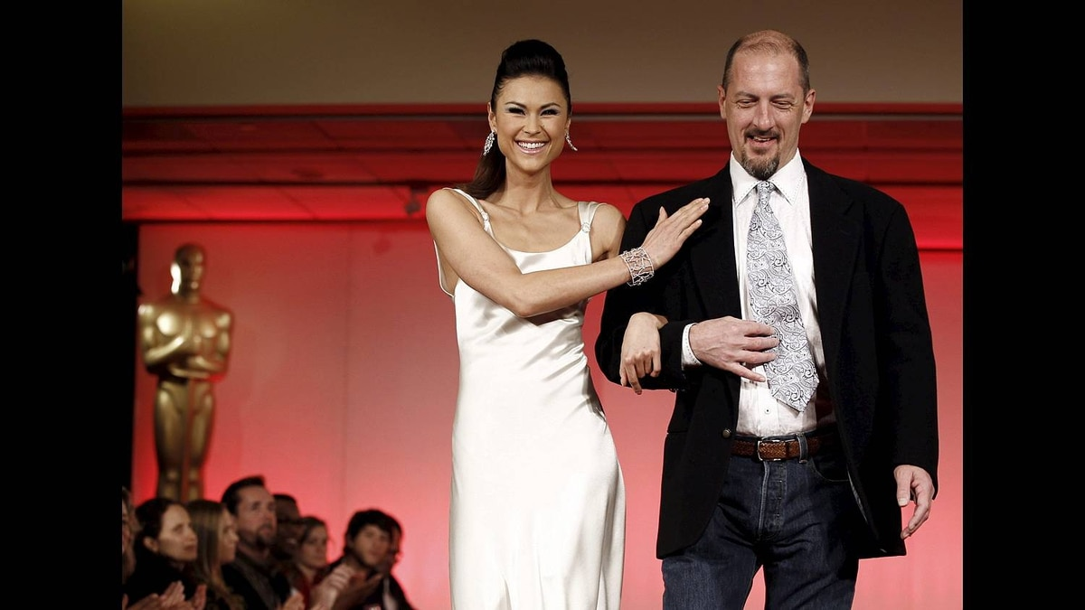 Designer Clay Sadler, right, and model Lisa Malambri, wearing a dress designed by him, walk the runway during the 83rd Academy Awards Oscars Designer Challenge fashion show at the Academy of Motion Picture Arts and Sciences in Beverly Hills, Calif., Tuesday, Feb. 15, 2011.
