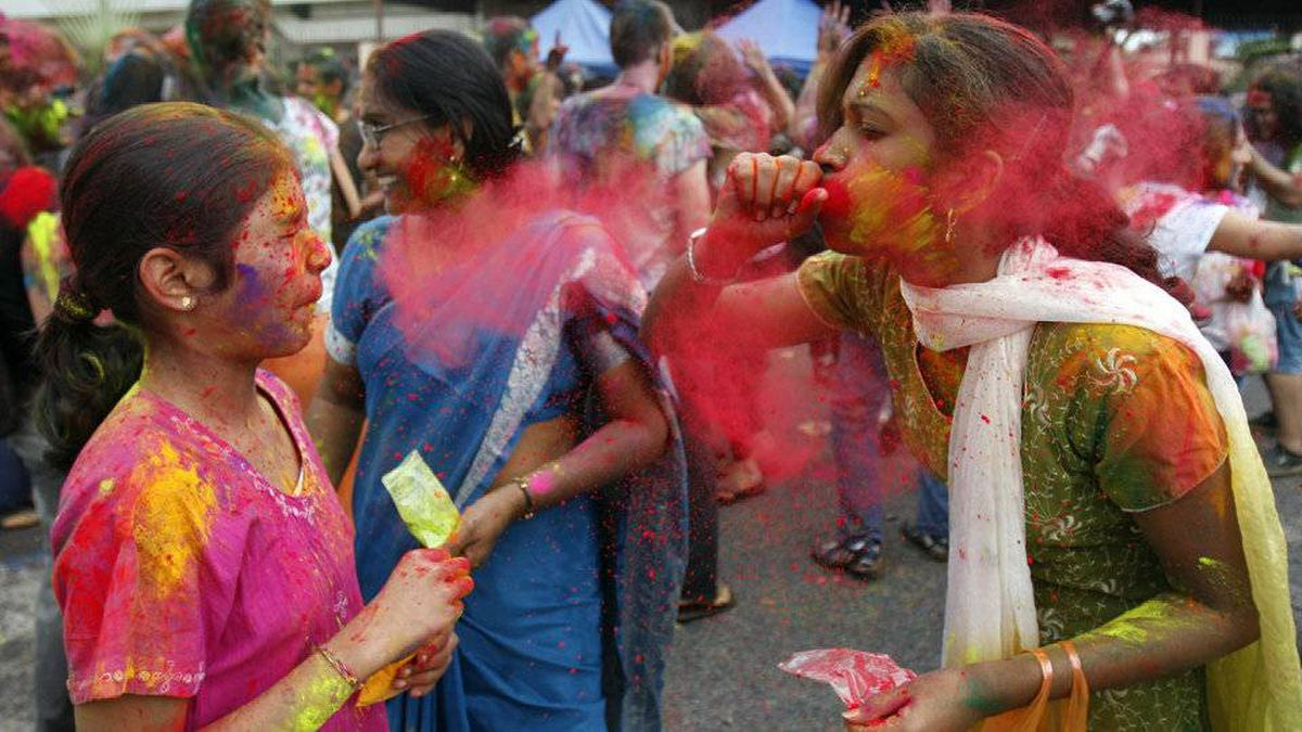 A woman blows coloured powder to a young girl. Holi, the Hindu festival of colours, is celebrated by people throwing coloured powder and water at each other.