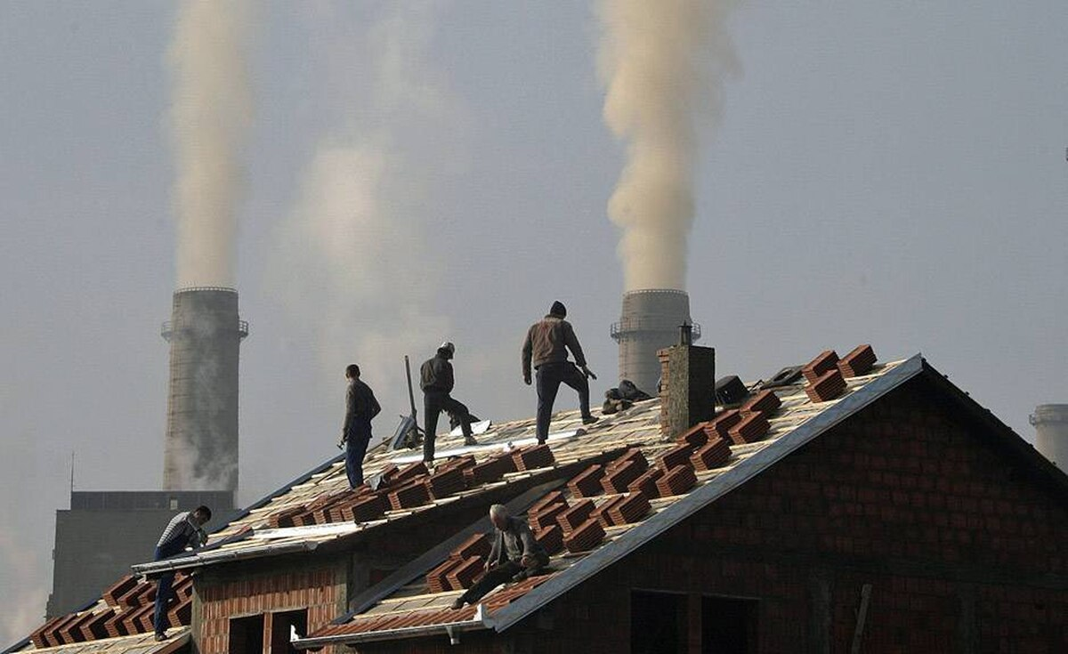 Workers build a house near the chimneys of the Kosova A power plant, the biggest polluter in the country, near Kosovo's capital Pristina, December 7, 2009. The biggest climate meeting in history, with 15,000 participants from 192 nations, begins in Copenhagen on Monday seeking to agree curbs on greenhouse gas emissions and raise billions of dollars for the poor in aid and clean technology.