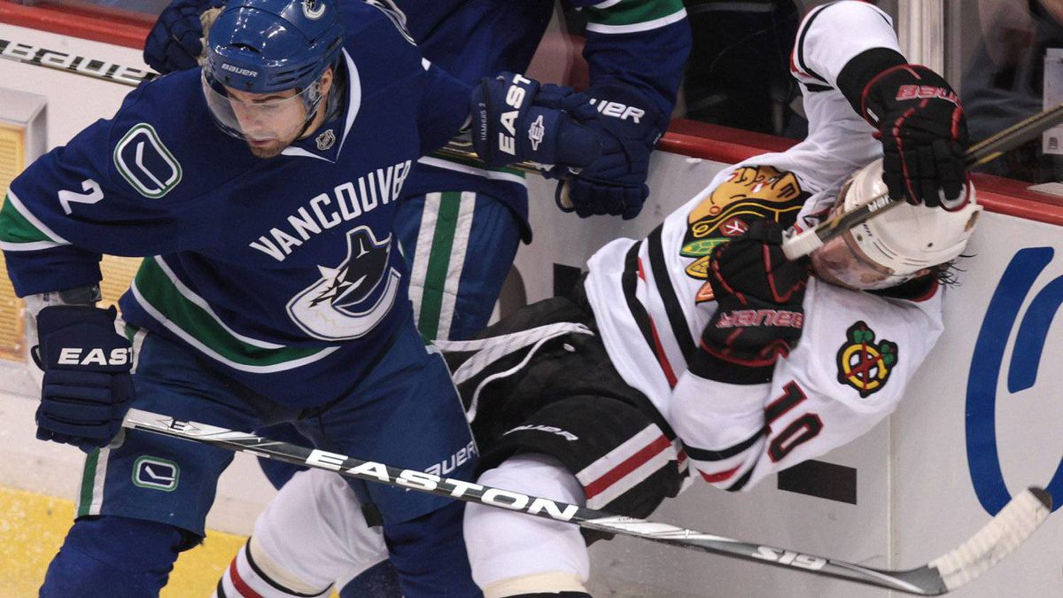 Vancouver Canucks' Dan Hamhuis, left, checks Chicago Blackhawks' Patrick Sharp. The Canucks won 4-3. THE CANADIAN PRESS/Darryl Dyck