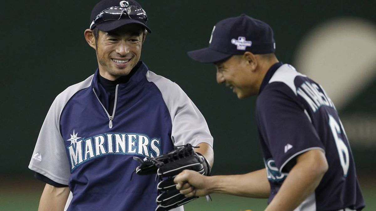 Seattle Mariners' Ichiro Suzuki and Munenori Kawasaki smile during a workout session for their American League season opening MLB baseball game against the Oakland Athletics in Tokyo.