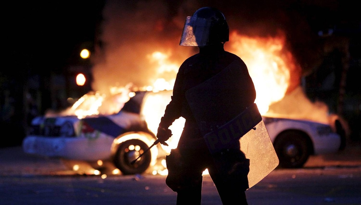 Riot officers on keep a perimeter around two burning police cars in downtown Vancouver June 15, 2011. (John Lehmann/The Globe and Mail)