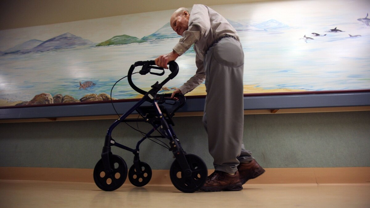 Broadmead Care Society resident Gene Seward walks through a hallway wearing track pants with a hip protector. A soft padded energy absorbent padding worn to prevent hip fractures.