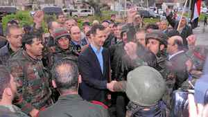 Syrian President Bashar al-Assad shakes hands with soldiers at the Baba Amr neighbourhood of Homs on Tuesday.