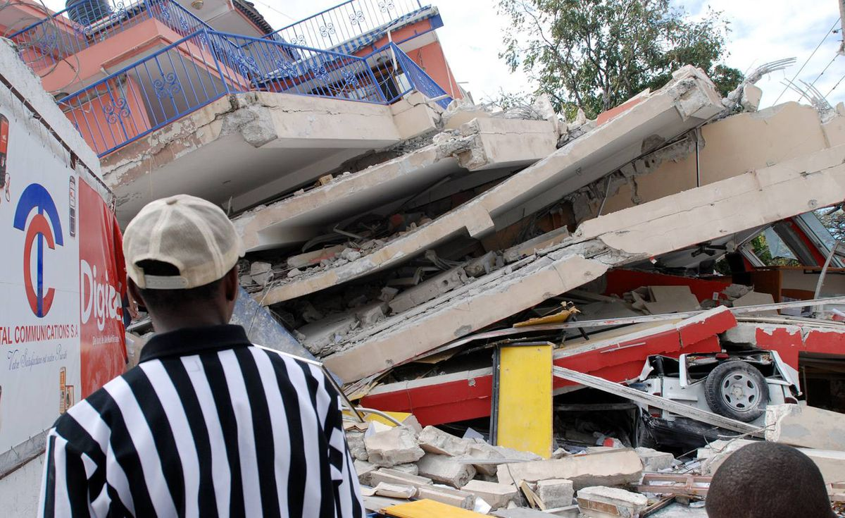 People look at the remains of a six-story communications building on Jan. 13, 2010 in Port-au-Prince, Haiti.