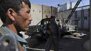 Afghan policemen keep watch near the wreckage of a burned-out vehicle at the UN headquarters in Mazar-i-Sharif on April 2, 2011, after protesters attacked the compound April 1.