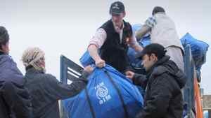 In this Thursday, Nov. 24, 2011 photo, an Afghan man, left, receives a sack containing humanitarian aid donated by International Organization for Migration (IOM) for drought-hit families in Mazar-e-Sharif, Balkh province, north of Kabul, Afghanistan.