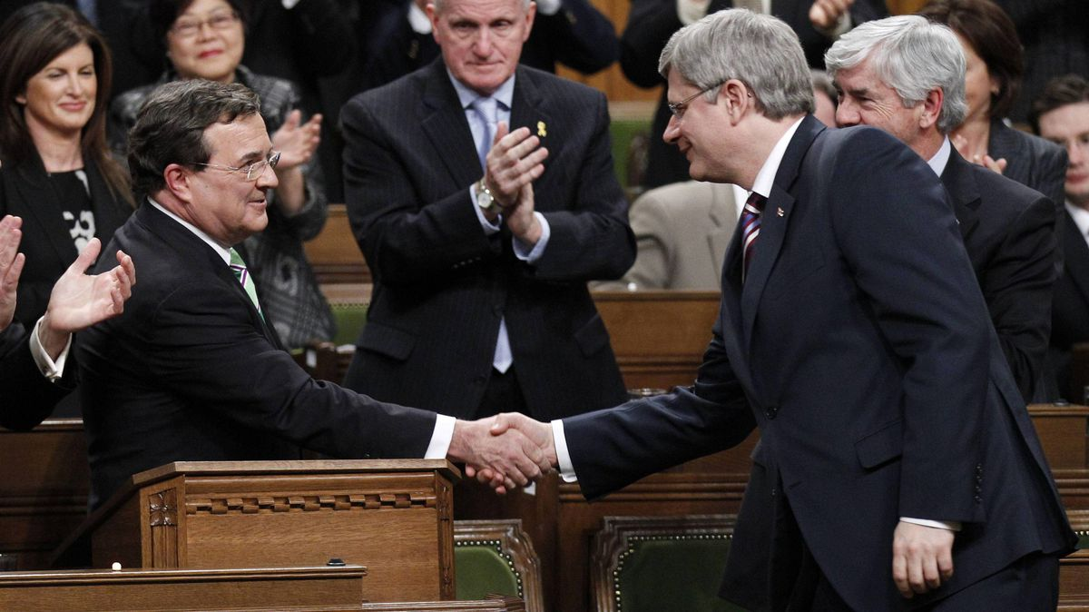 Finance Minister Jim Flaherty shakes hands with Prime Minister Stephen Harper in the House of Commons on Parliament Hill in Ottawa March 22, 2011.