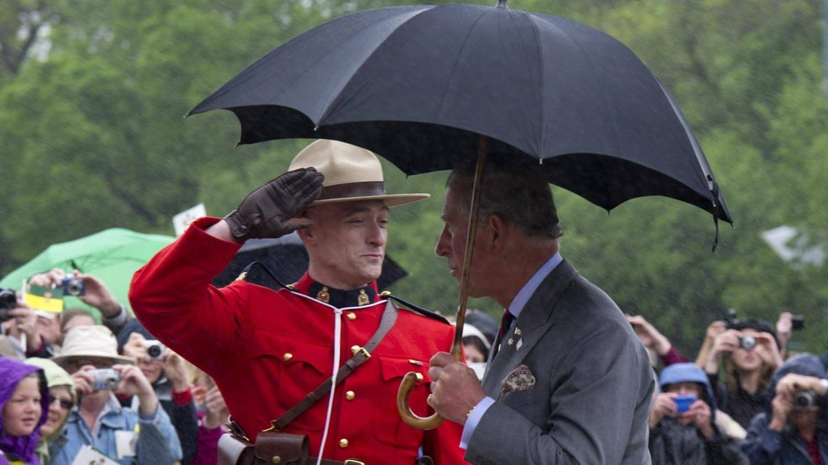 Prince Charles is saluted by a member of the RCMP as he arrives at the Saskatchewan Legislature during a light downpour in Regina, on May 23, 2012 .
