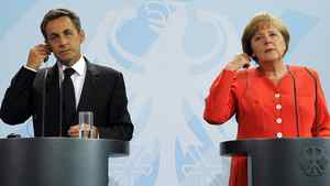 French President Nicolas Sarkozy (L) and German Chancellor Angela Merkel adjust their earpieces as they address a news conference at the Chancellery in Berlin June 17, 2011.