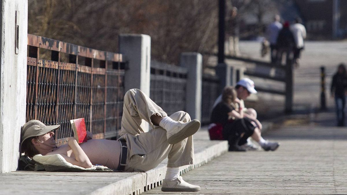 Steven Anderson reads a book and enjoys the sunshine on a bridge at Cedarvale Park in Toronto on Sunday, March 11, 2012.