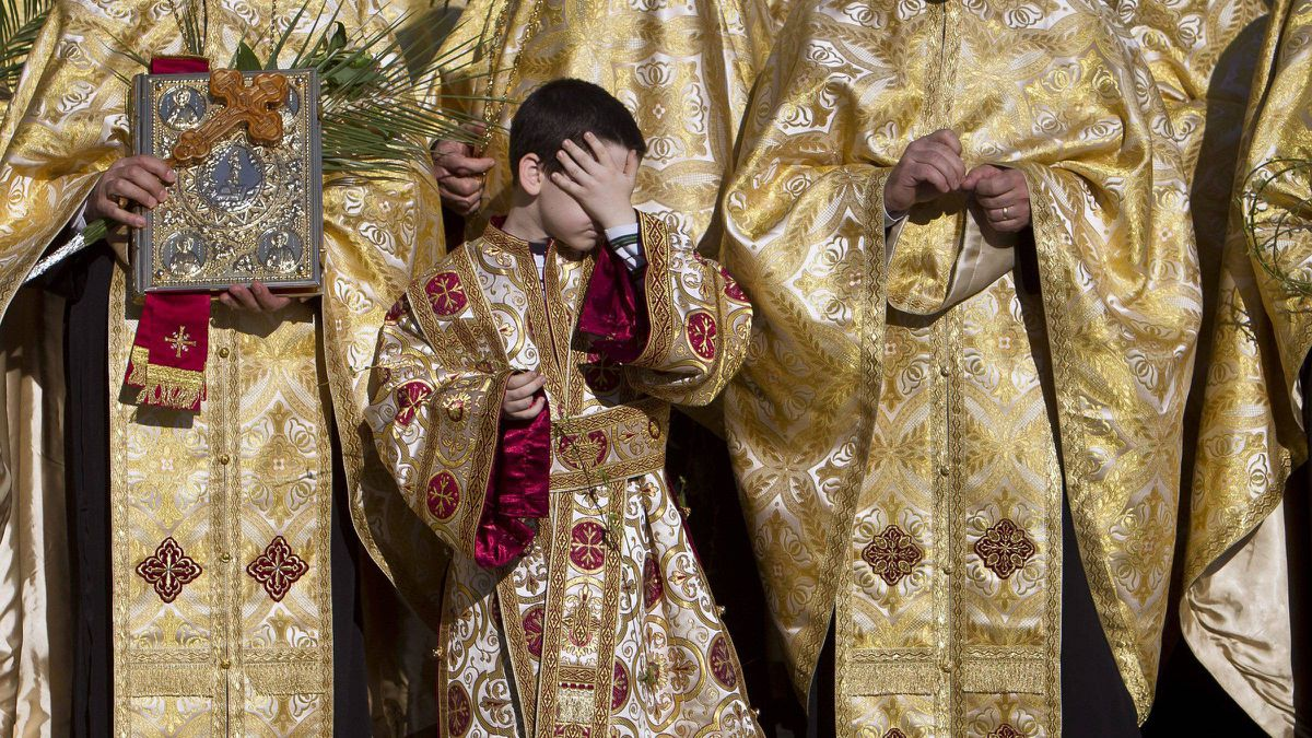 A boy shields his face from the sun during an orthodox Palm Sunday pilgrimage in Bucharest on Saturday afternoon.
