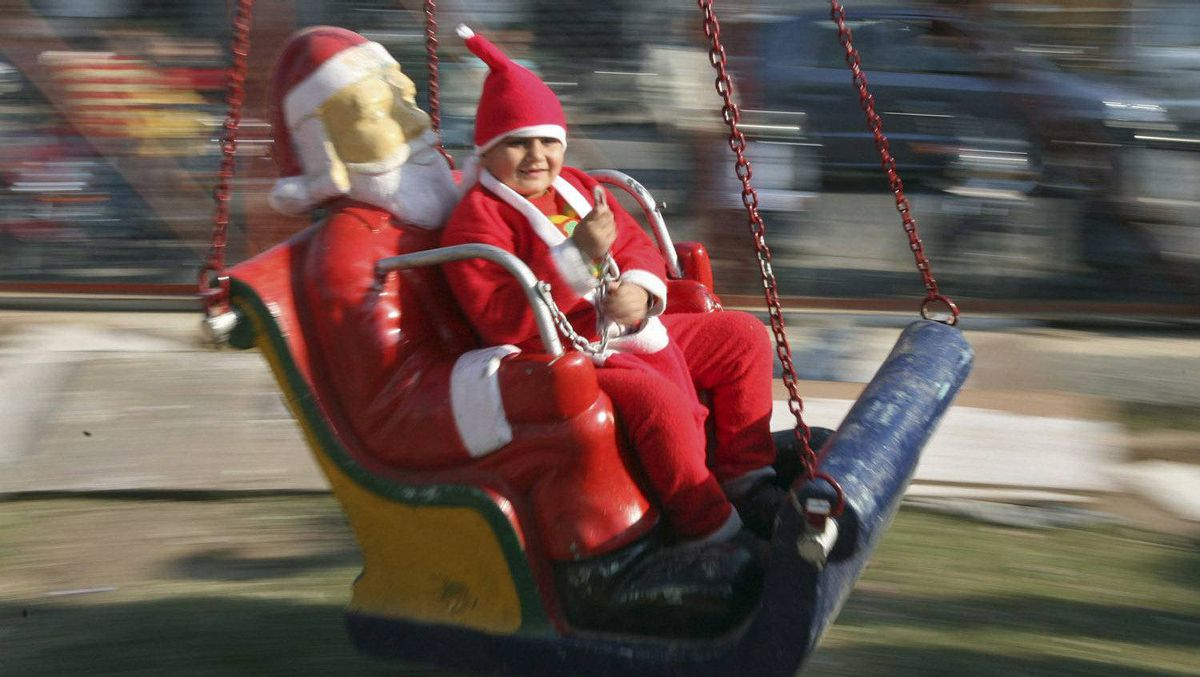 A boy dressed in a Santa Claus costume rides on a merry-go-round outside a church during Christmas celebrations in Jammu December 25, 2011.