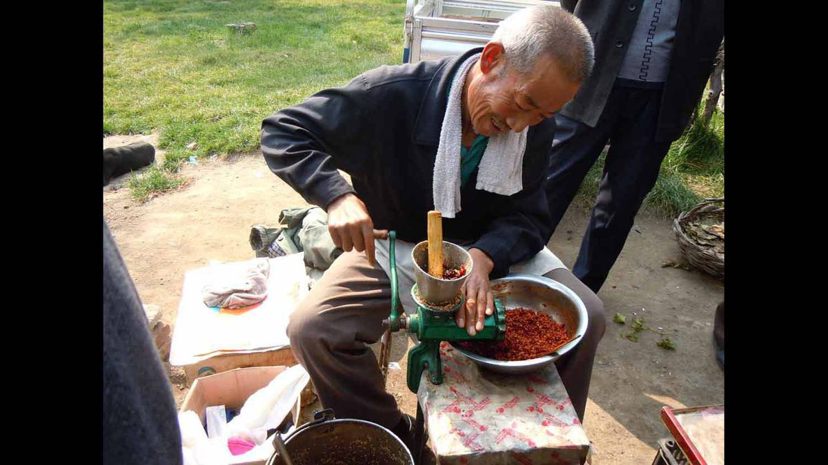 This man is grinding clili peppers for sale in the province of Xian in China