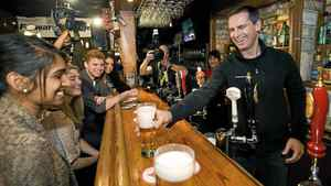 Ontario Premier Dalton McGuinty serves beer after speaking about his party's plan to make post-secondary education more accessible and affordable while at the Regal Beagle pub.