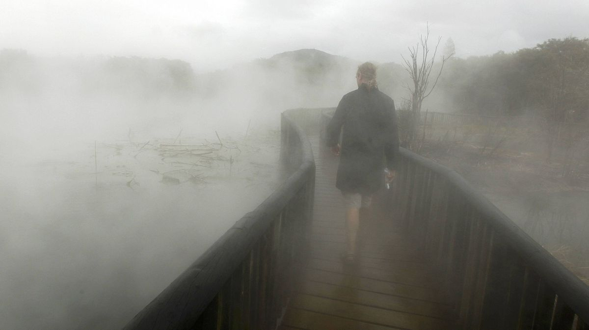 A tourist walks through steam on a bridge above thermal water in a park in Rotorua September 25, 2011. The geothermal activity and bubbling mud volcanoes are the main attractions of the central area of the northern island of New Zealand.