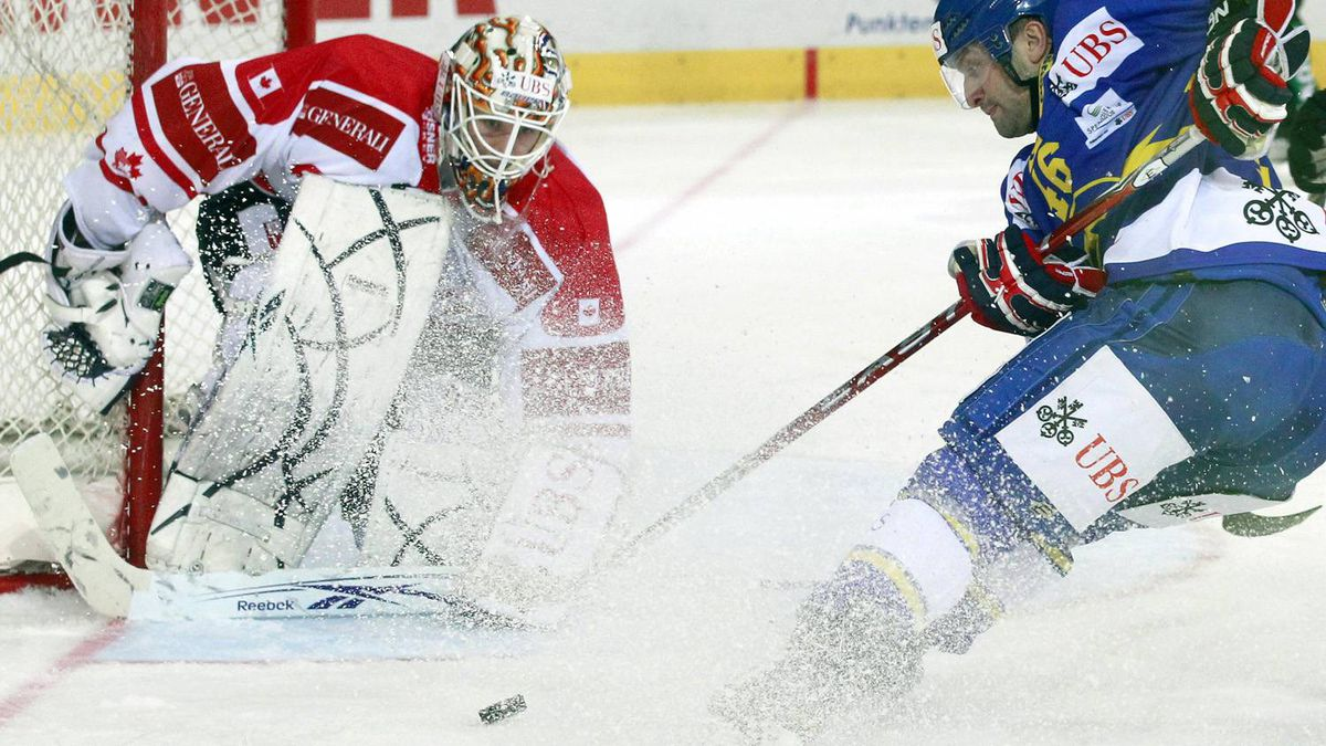 Team Canada's goalkeeper Jeff Deslauriers (L) is challenged by Paolo Duca of HC Davos scores during their ice hockey match at the Spengler Cup tournament in the Swiss mountain resort of Davos December 28, 2010