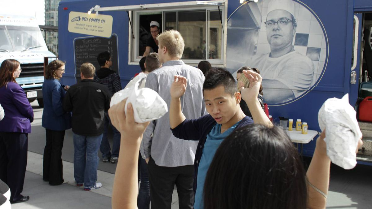 A young woman does mock exercises with two sandwiches from the Caplansky's truck at the Food Truck Rally at Celebration Square.