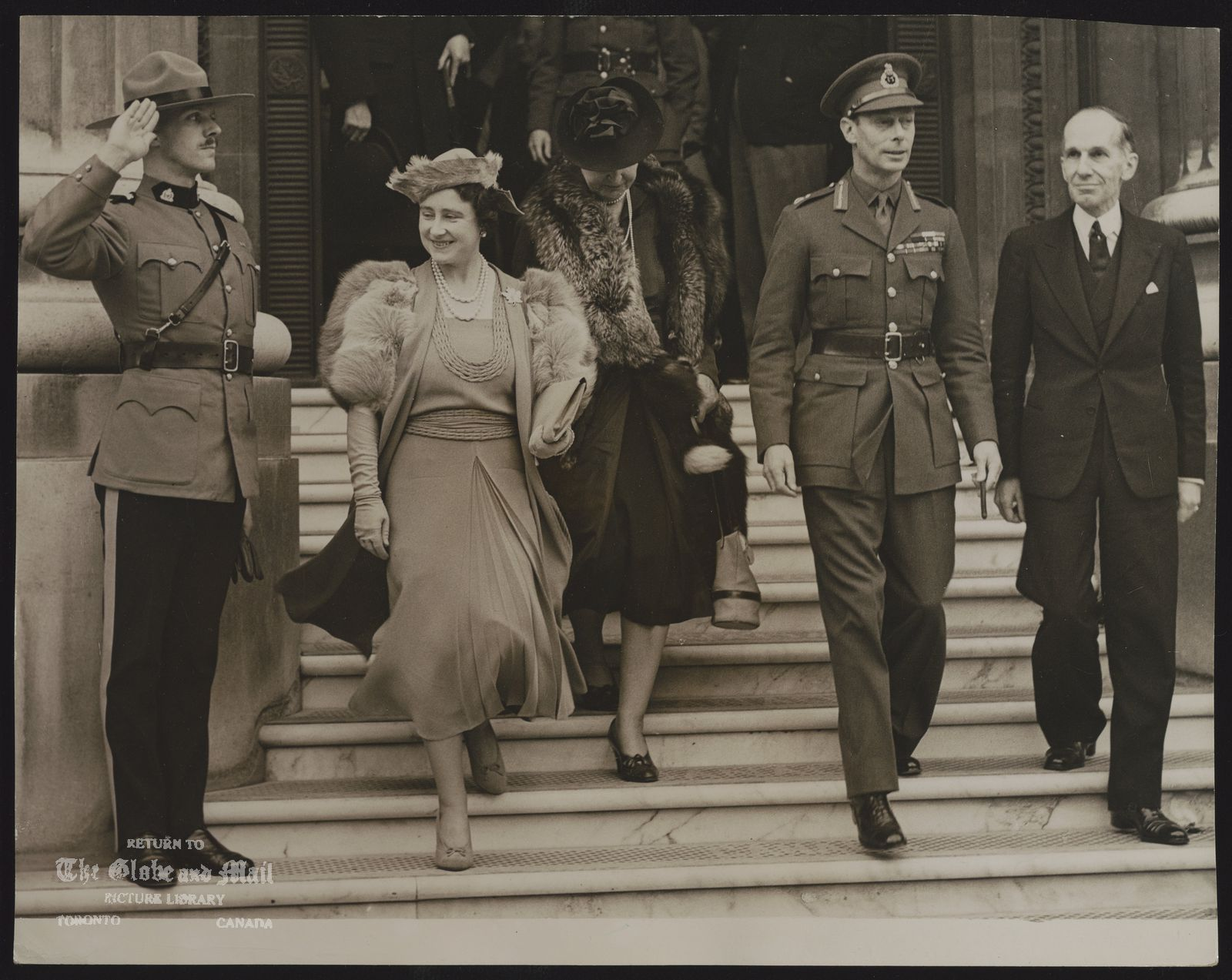 The notes transcribed from the back of this photograph are as follows: ROYAL FAMILY GREAT BRITAIN KING GEORGE VI & QUEEN ELIZABETH KING AND QUEEN VISIT CANADA HOUSE [IN LONDON]. THE KING AND QUEEN VISITED CANADA HOUSE, LONDON (THE HEADQUARTERS OF THE DOMINION) THIS AFTERNOON, OCTOBER 18, [1939]. THEY INSPECTED THE WORK DONE BY THE WORK ROOM ORGANISED BY THE WIFE OF HIGH COMMISSIONER VINCENT MASSEY. BABY CLOTHES AND KNITTED WEAR FOR THE TROOPS WERE SHOWN. ASSOCIATED PRESS PHOTO SHOWS: THE KING AND QUEEN LEAVING CANADA HOUSE THIS AFTER NOON, OCTOBER 18, SALUTED BY THE GUARD OF THE ROYAL CANADIAN MOUNTED POLICE. LEFT TO RIGHT; THE QUEEN; MRS. VINCENT MASSEY; THE KING; HIGH COMMISSIONER VINCENT MASSEY.