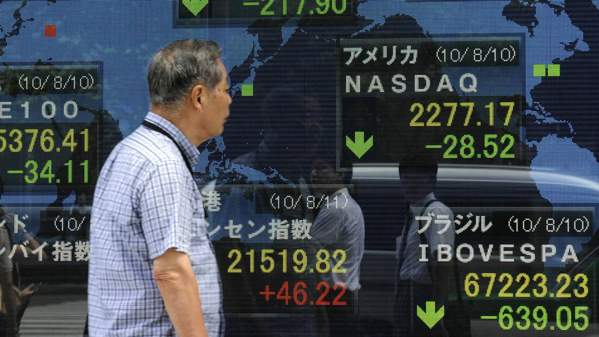 A man looks at an electric quotation board flashing key indexes of main stock exchanges in front of a securities company in Tokyo on August 11, 2010