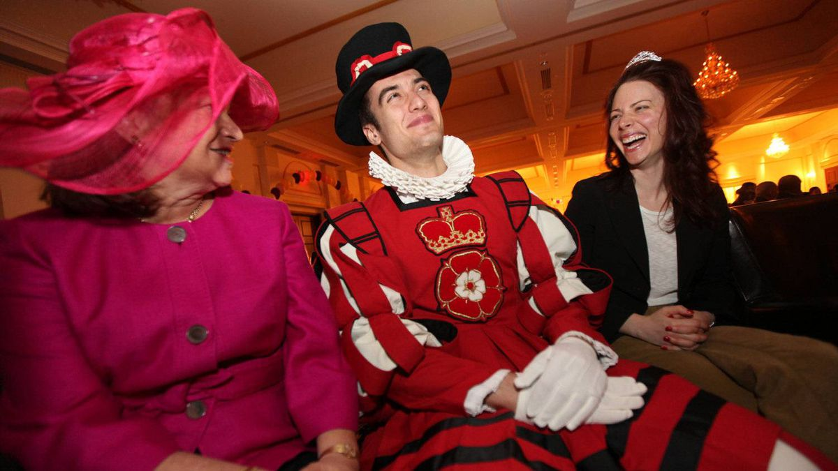 Bonnie Lax, left, and her daughter Sandra Lax, right, share a laugh with employee Peter Kazakis in his Yeoman guard outfit at On The Park event centre in Toronto while watching the wedding of William and Kate Middleton Friday April 29, 2011.