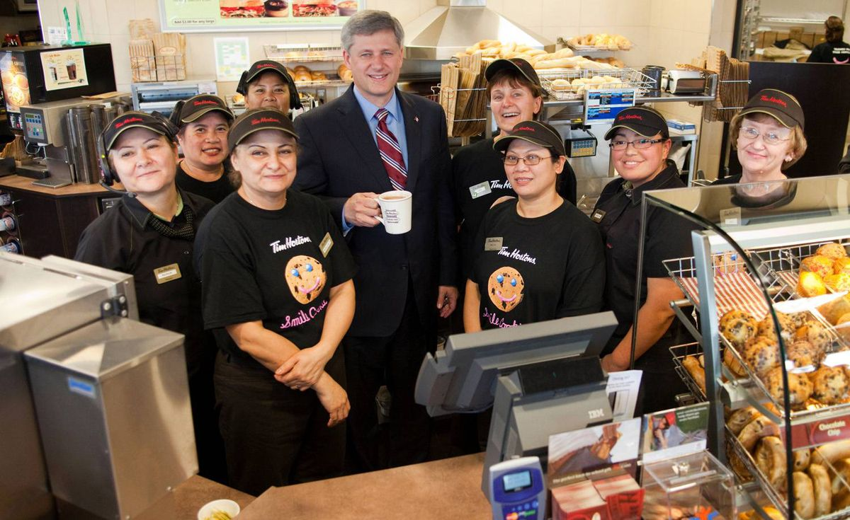 """This feel-good photo of Stephen Harper surrounded by the staff of a Tim Hortons in Oakville, Ont., was taken and distributed by the Prime Minister's Office on Sept. 23. The Prime Minister travelled to Tim Hortons' Oakville offices to celebrate the fact that lowered tax rates had prompted the coffee and doughnut giant to move its corporate offices back to Canada. The PMO's caption on its photo read: """"Prime Minister Stephen Harper celebrates the return of Tim Hortons to Canada with store staff."""" It was one of two photos issued by the PMO that day."""