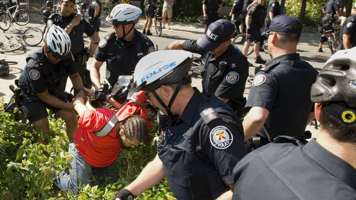 A protester is arrested by police following protest in Toronto on June 21, 2010. The small group of demonstrators marched from Allen Gardens through the downtown core and to the Children's Aid Society building near Yonge and College streets as part of an anti G8/20 protest.