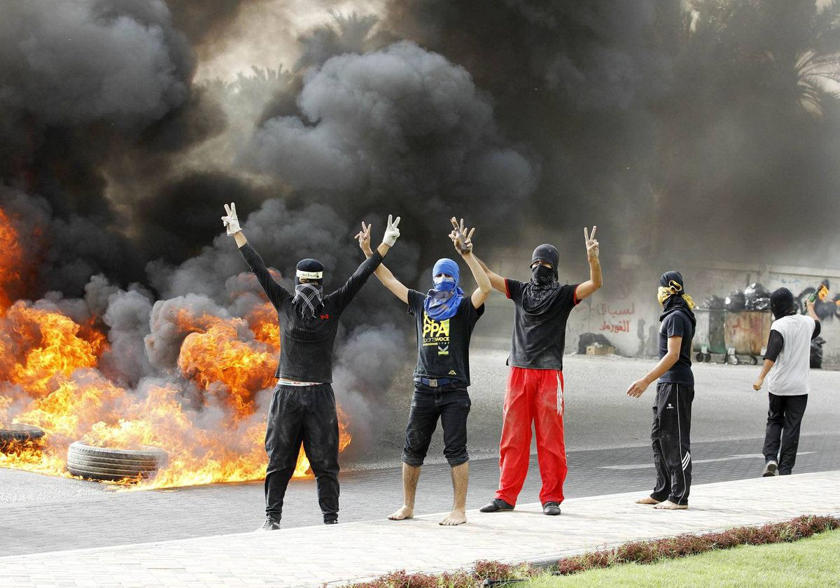 Anti-government protesters flash victory signs as they burn tyres in Budaiya, west of Manama, early April 22, 2012.