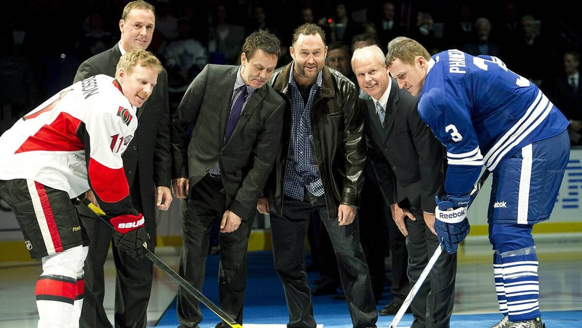 Hockey Hall of Fame inductees Joe Nieuwendyk, back left, Doug Gilmour, back second left, Ed Belfour, centre back, Mark Howe, back left, take part in a puck drop ceremony with Toronto Maple Leafs defenceman Dion Phaneuf, front right, and Ottawa Senators Daniel Alfredsson, front left, before the start of NHL hockey action in Toronto on Saturday, Nov. 12, 2011. THE CANADIAN PRESS/Nathan Denette
