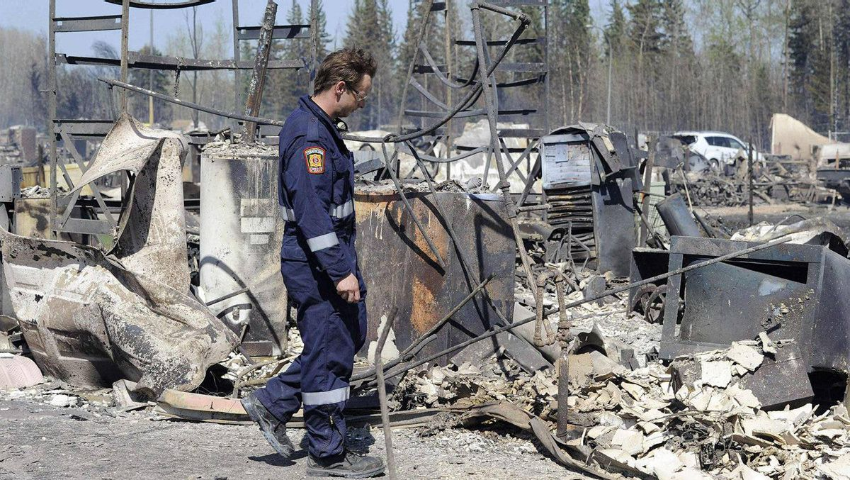 A fire-fighter from the Strathcona fire department searches for hot spots at a destroyed neighborhood in Slave Lake, Alberta May 16, 2011.