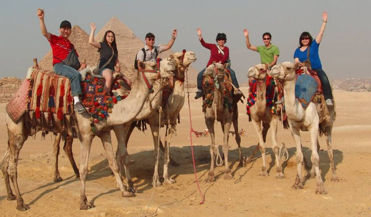 """Every year, the Winnipeg-based Cheung family embark on a family trip. In this photo taken in October 2010, the group smiles and waves for the camera atop camels near the Giza Pyramids in Egypt. When it comes to choosing the destination, there's only one rule, exlains Mr. Cheung. """"We have to go somewhere we've never been before."""" Over the past few years, they've had the chance to visit China, Ireland, Hawaii and Costa Rica"""
