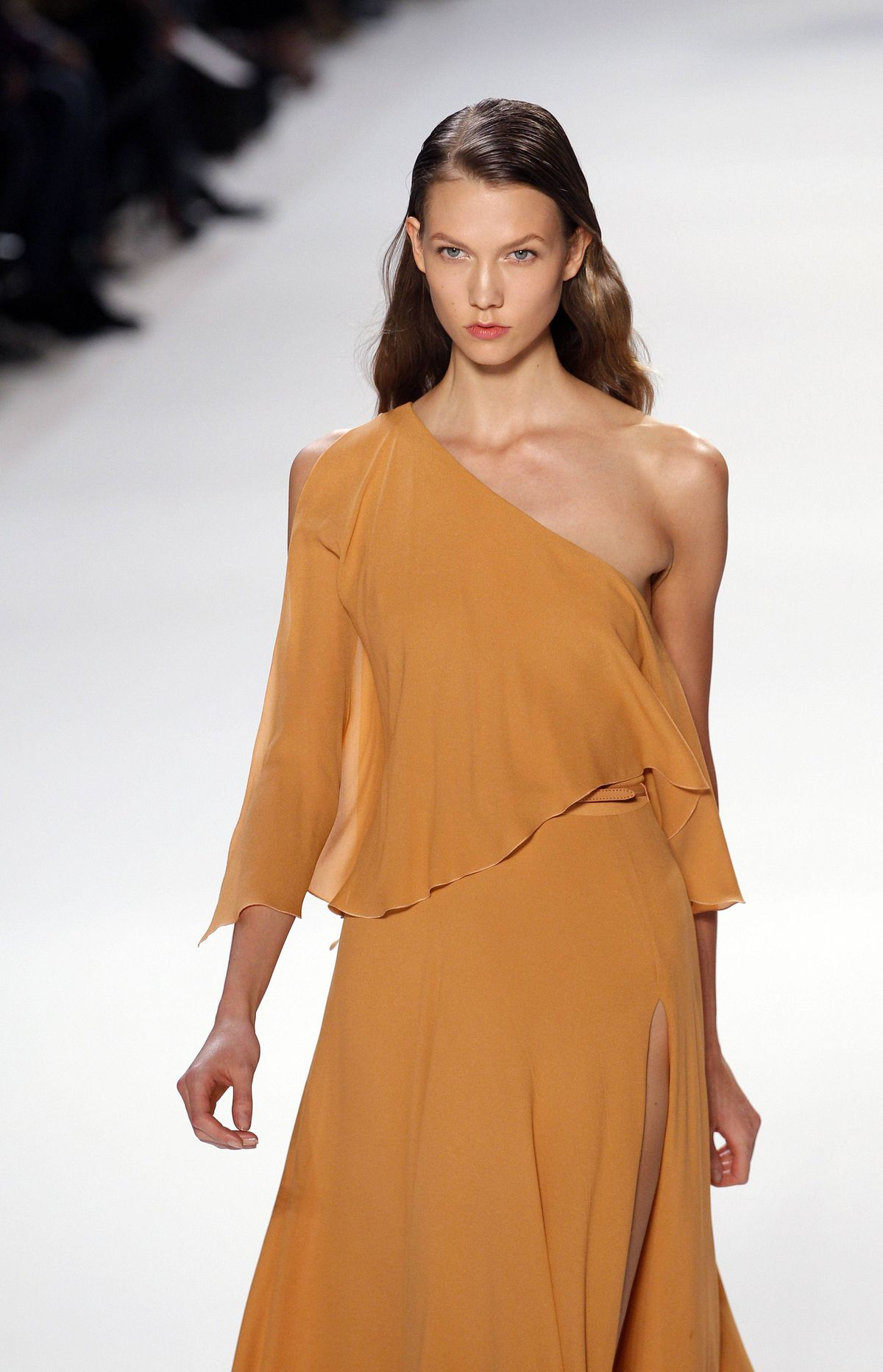 Saab did offer some daywear options in pleated crepe georgette, chiffon and lace, sans sparkle. The jumpsuits were extra flowy. Model Karlie Kloss is wearing a one-shouldered dress.