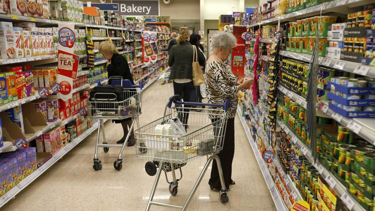 Customers shop for groceries in a supermarket in London.