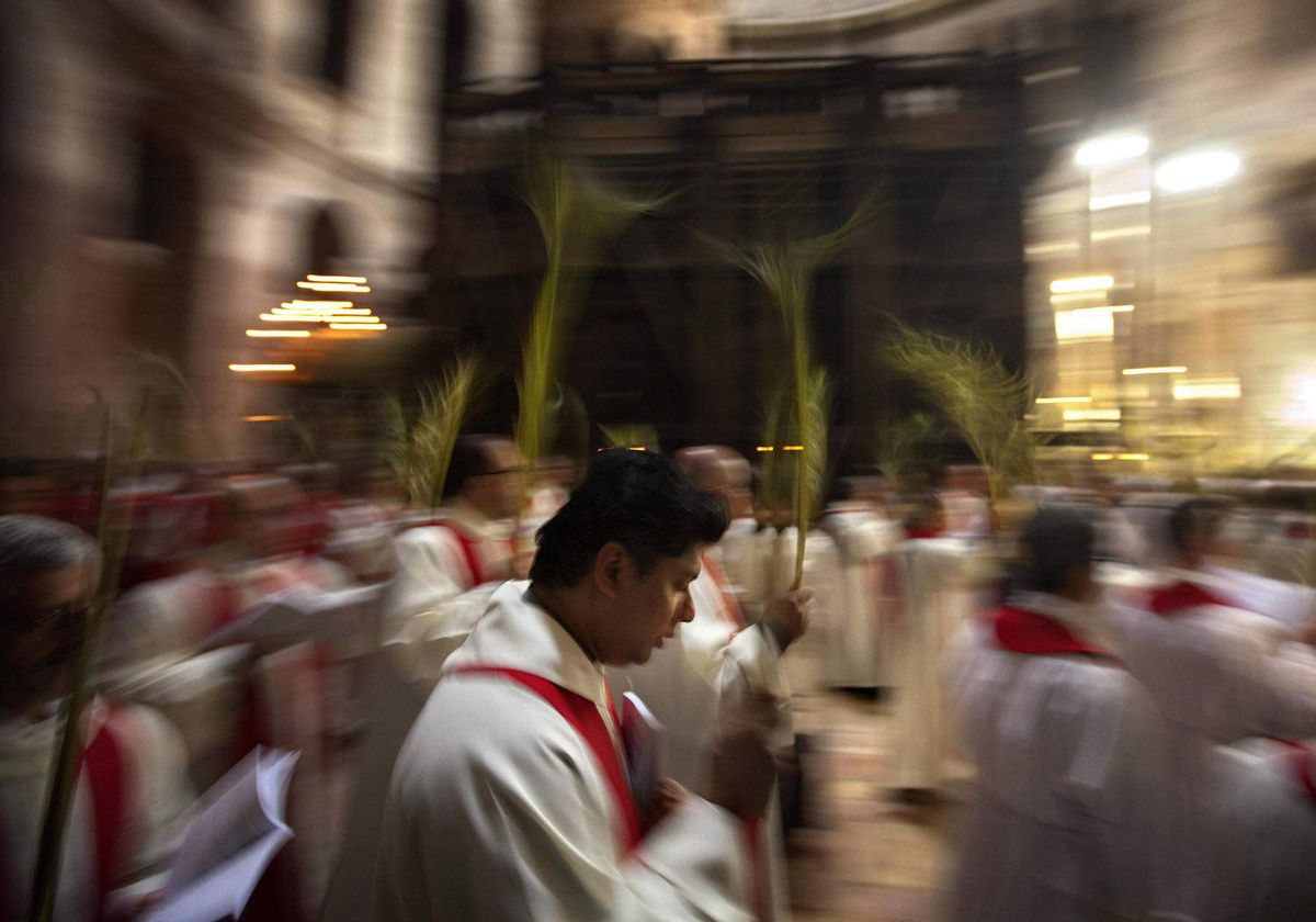 Catholic priests carry palm fronds at Church of the Holy Sepulchre, traditionally believed by many to be the site of the crucifixion and burial of Jesus Christ, in Jerusalem's Old city, Sunday, April 1, 2012.