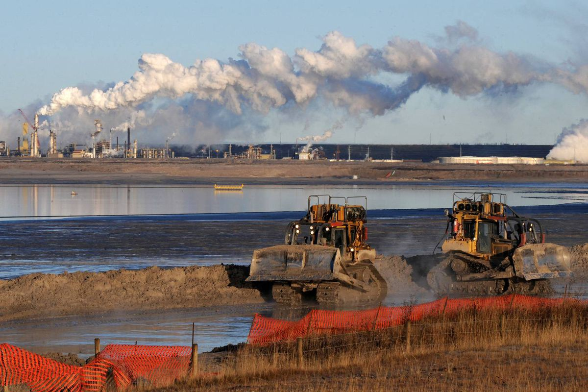 Workers use heavy machinery in the tailings pond at the Syncrude oil sands extraction facility near the town of Fort McMurray in Alberta Province, Canada on October 25, 2009.