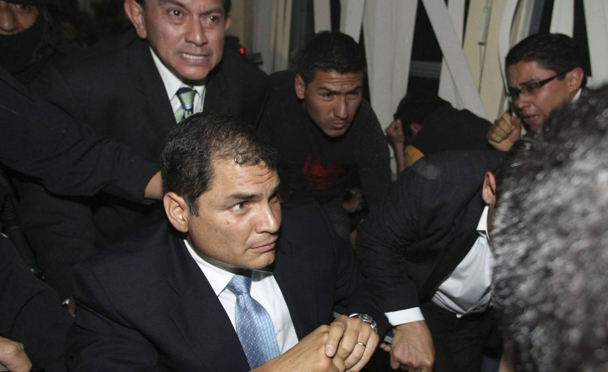 Ecuador's President Rafael Correa, bottom, is rescued by security officers from a hospital where he was holed up by protesting police in Quito. Dolores Ochoa/AP