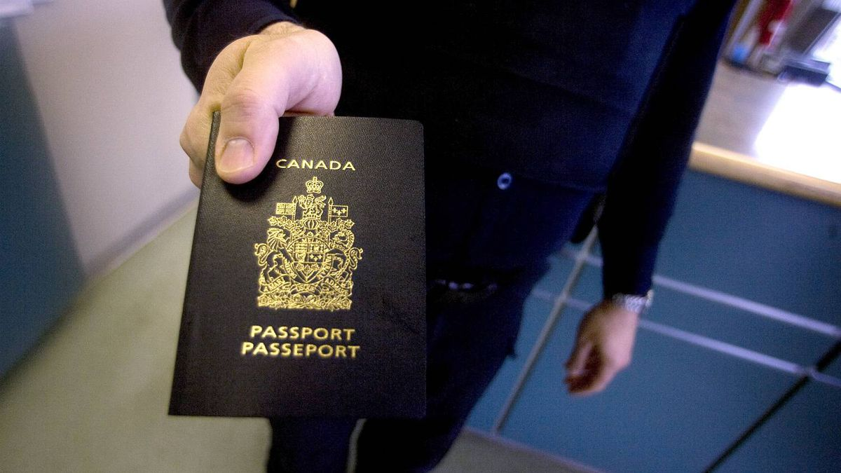 A Canadian Customs guard holds a passport in Stanstead, Que, on May 10, 2009.