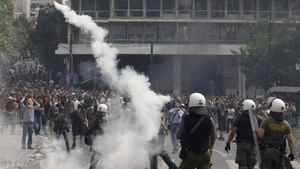Policemen throw tear gas at protesters during riots around Constitution (Syntagma) square in Athens June 15, 2011. Greek Prime Minister George Papandreou offered Wednesday to step down and make way for a national unity government if the opposition agreed on a clear plan on how to proceed with reforms, government sources said.