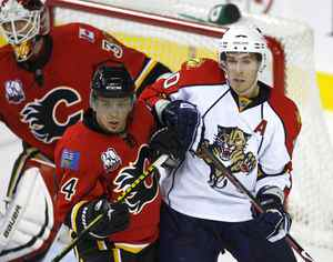 Calgary Flames' Theo Fleury, left, battles with Florida Panthers' David Booth in front of Calgary goalie Miikka Kiprusoff, from Finland, during second period preseason NHL hockey action in Calgary on Sunday Sept. 20, 2009 THE CANADIAN PRESS/Larry MacDougal