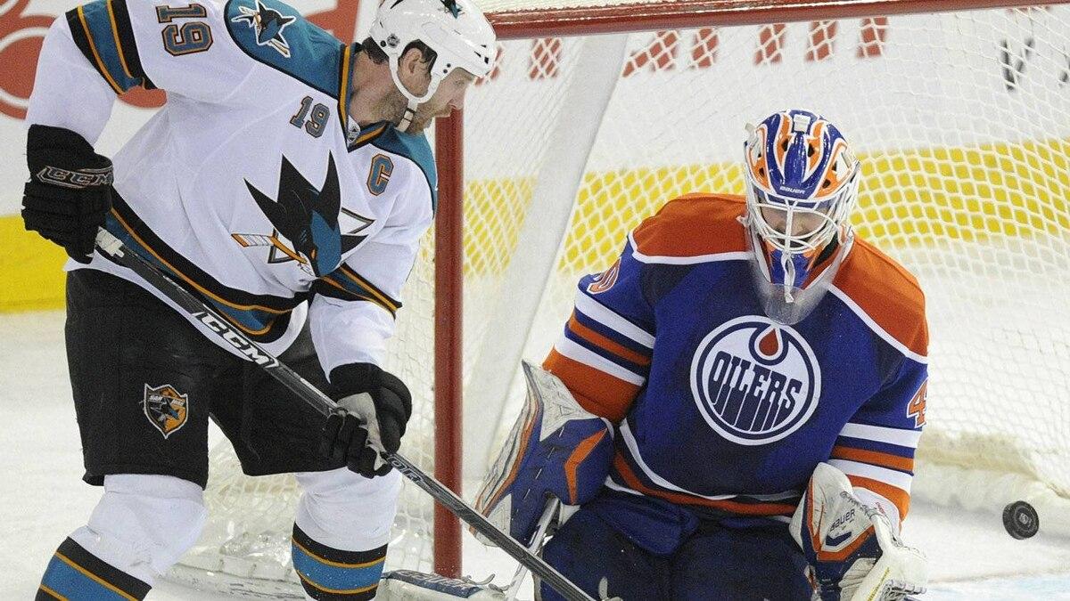 San Jose Sharks Joe Thornton, left, releases a shot at Edmonton Oilers' goalie Devan Dubnyk during the third period of NHL hockey in Edmonton on Monday, March 12, 2012. THE CANADIAN PRESS/John Ulan