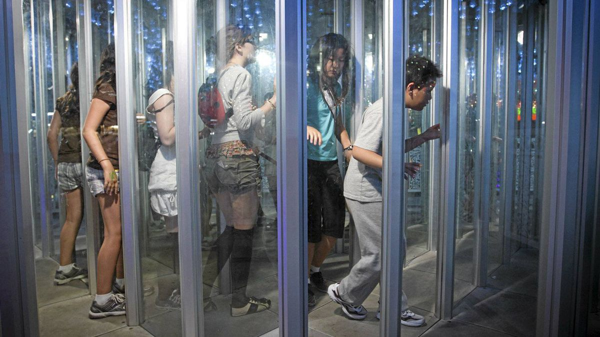Fair goers make their way though a maze of glass in a fun house at the Pacific National Exhibition in Vancouver, Aug. 20, 2011.